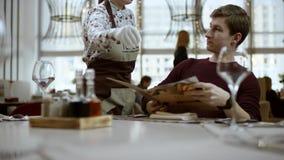 Camarero que da el menú a un hombre, almuerzo de negocios, servicio del restaurante el hombre se está sentando en un café mode almacen de metraje de vídeo