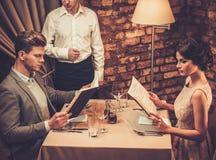 Camarero que explica el menú a los pares elegantes en restaurante Foto de archivo libre de regalías
