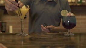 Camarero que hace el cóctel alcohólico con hielo machacado en el contador de la barra en café Camarero que inserta la paja en beb almacen de video