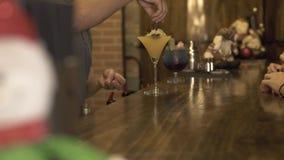 Camarero que hace el cóctel alcohólico para el cliente en la tabla de la barra en pub Camarero que adorna el cóctel de la bebida  metrajes