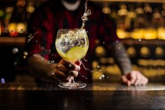 Camarero que hace el chapoteo de un cóctel delicioso de Gin Tonic con l imagen de archivo