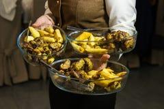 Camarero que lleva tres placas con el plato de la carne y las patatas en cierto acontecimiento, partido o recepción nupcial festi imágenes de archivo libres de regalías