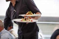 Camarero que lleva una placa con el plato de la ensalada en una boda. Imagenes de archivo