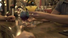 Camarero que pone el cóctel alcohólico en la tabla de la barra para el cliente en la igualación del café Gente que toma el vidrio metrajes