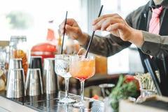 Camarero que prepara diversos cócteles que se mezclan con la paja dentro de la barra - concepto de la profesión, del trabajo y de fotos de archivo
