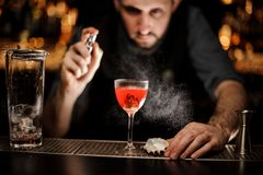 Camarero que rocía en el cóctel rojo transparente delicioso en el vidrio foto de archivo