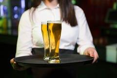 Camarero que sirve dos vidrios de cerveza fotos de archivo libres de regalías