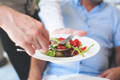 Camarero que sirve una placa de la ensalada griega Foto de archivo libre de regalías