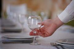 Camarero que sostiene copas de vino vacías Fotografía de archivo