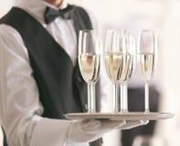 Camarero que sostiene la bandeja con champán en fondo borroso, fotografía de archivo