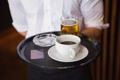 Camarero que sostiene la bandeja con la taza de café y la pinta de cerveza Fotografía de archivo