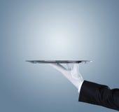 Camarero que sostiene la bandeja de plata vacía foto de archivo