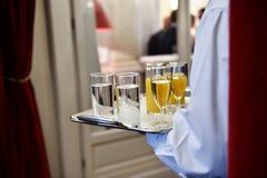Camarero que sostiene una bandeja con las bebidas durante el cóctel Imagen de archivo