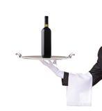 Camarero que sostiene una bandeja de plata con un vino rojo Foto de archivo