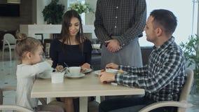 Camarero que toma la orden en la tabla de familia que cena junta Ellos que parecen felices y satisfechos imagenes de archivo