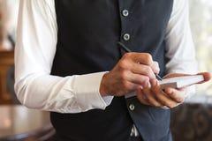 Camarero que toma una orden que lleva un chaleco Foto de archivo libre de regalías