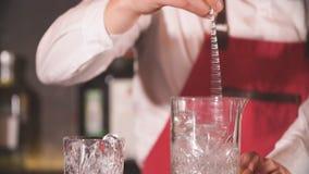 Camarero que usa la cuchara larga del metal para mezclar los cubos de hielo con la bebida en un vidrio almacen de video