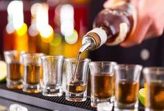 Camarero que vierte alcohol duro en los vidrios imagen de archivo