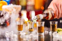 Camarero que vierte alcohol duro en los vidrios foto de archivo