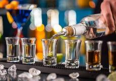Camarero que vierte alcohol duro en los vidrios fotos de archivo libres de regalías