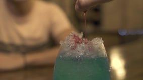 Camarero que vierte el licor rojo en el hielo mientras que hace el cóctel alcohólico en el contador de la barra en pub Cierre enc metrajes