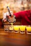 Camarero que vierte la bebida alcohólica fuerte en los pequeños vidrios en b foto de archivo libre de regalías