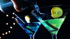 Camarero que vierte la bebida azul y amarilla en una tabla de la barra del disco, atmósfera del cóctel del disco almacen de video