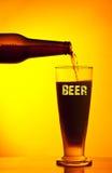 Camarero que vierte la cerveza oscura Imagenes de archivo