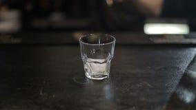 Camarero que vierte un whisky escocés con hielo en la barra Tirado con el resbalador almacen de metraje de vídeo