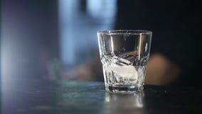 Camarero que vierte un whisky escocés con hielo en la barra Tirado con el resbalador metrajes