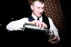 Camarero que vierte una bebida fotos de archivo
