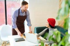 Camarero Serving Young Woman en café fotos de archivo