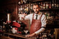 Camarero sonriente pourring un cóctel transparente en el cockt foto de archivo