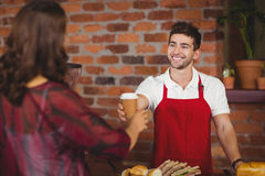 Camarero sonriente que sirve un café a un cliente Foto de archivo libre de regalías