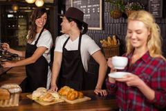 Camarero sonriente que sirve un café a un cliente Fotos de archivo