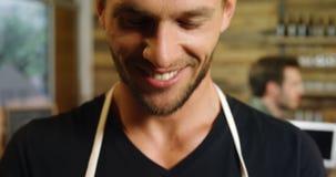 Camarero sonriente que sostiene una taza de café en el café 4k almacen de metraje de vídeo