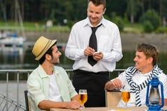 Camarero sonriente que toma orden de clientes de los hombres Imagen de archivo libre de regalías