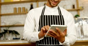 Camarero sonriente que usa la tableta digital 4 4k almacen de metraje de vídeo
