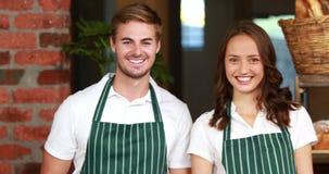 Camarero y camarera sonrientes que gesticulan los pulgares para arriba almacen de metraje de vídeo