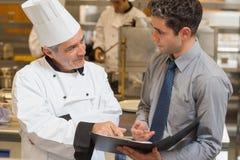 Camarero y cocinero que discuten el menú Foto de archivo