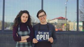 Camareros atractivos felices que sostienen la pizarra abierta y que miran ventanas del café nuevamente abierto entonces que da vu almacen de video