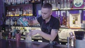 Camareros profesionales en el mixixng de la barra con los cubos de hielo largos de la cuchara en el vidrio Party el tiempo almacen de video