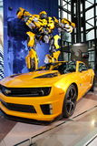 Camaro & Transformer At NY International Auto Show. Beautiful yellow Camaro and huge Transformer (from the Transformers 3 Movie) at the NY International Auto Stock Images
