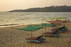 Camas azuis vazias da praia sob toldos da cor na areia amarela na perspectiva do mar e da ilha verde com a casa imagem de stock