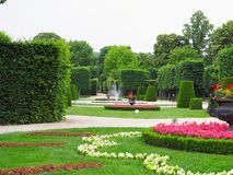 Camas de flor ideais abstratas e árvores tosquiado no parque bem conservado Imagem de Stock
