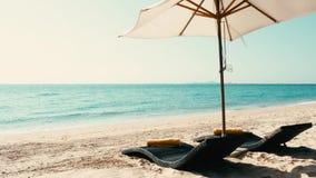 Camas de la playa con el paraguas en la arena y mar con el cielo azul almacen de metraje de vídeo