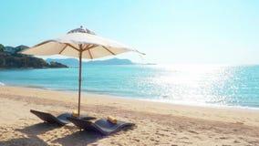 Camas de la playa con el paraguas en la arena y mar con el cielo azul