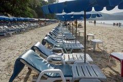 Camas de Sun com os guarda-chuvas na praia com areia branca, em Tailândia fotografia de stock