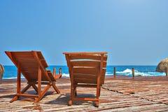 Camas de Sun em uma ponte de madeira no mar Imagens de Stock Royalty Free