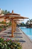Camas del tablón debajo de los paraguas en la piscina en hotel Egipto Fotos de archivo libres de regalías